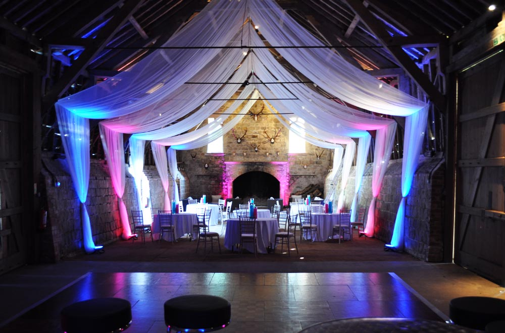 Wick Bottom barn sail ceiling voile drapes with coloured uplighters for a party or wedding