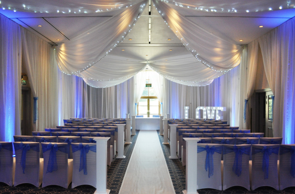 Wall and Ceiling drapes for a wedding ceremony with Blue chair sashes and uplighting on the drapery at Bowood Hotel spa and Golf Club
