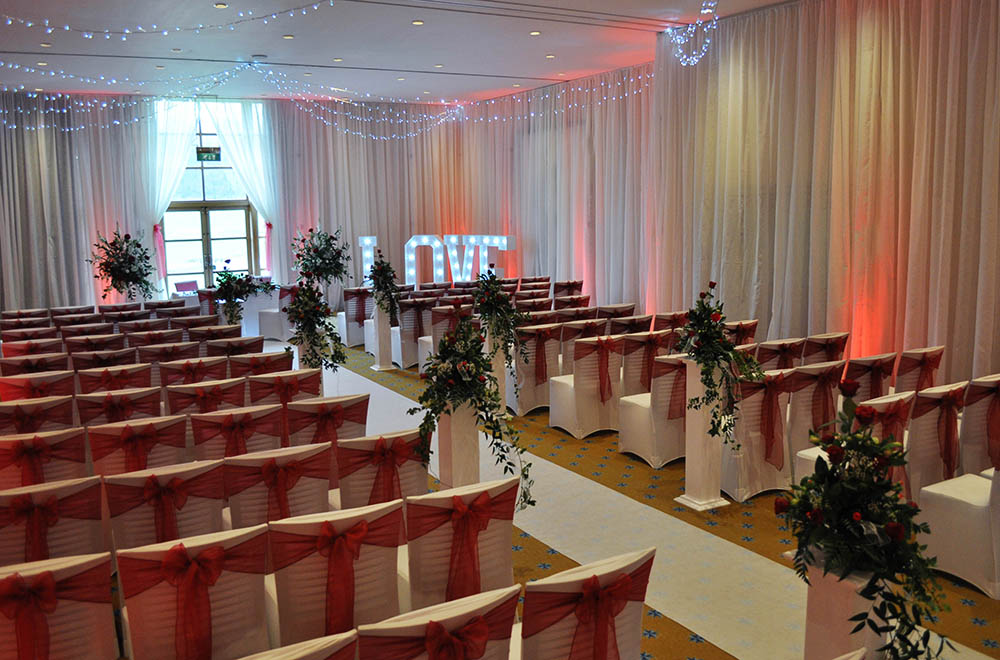 Red uplighting and chair cover sashes with full room drapes and white aisle runner at a wedding at Bowood Hotel, spa and gold club.