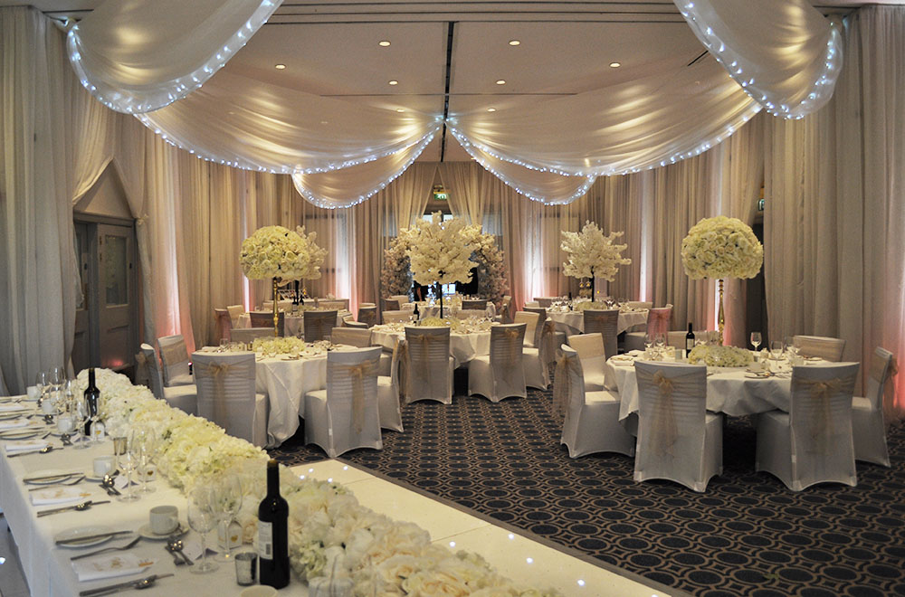 Wedding wall drapes at Bowood Golf Club and Hotel with uplighting and ceiling drapes with fairy lights.