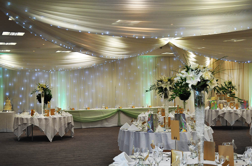 Starlit wedding drapes with Ceiling and wall drapery with integrated fairy lights at De Vere Cotswold Water Park Hotel and spa
