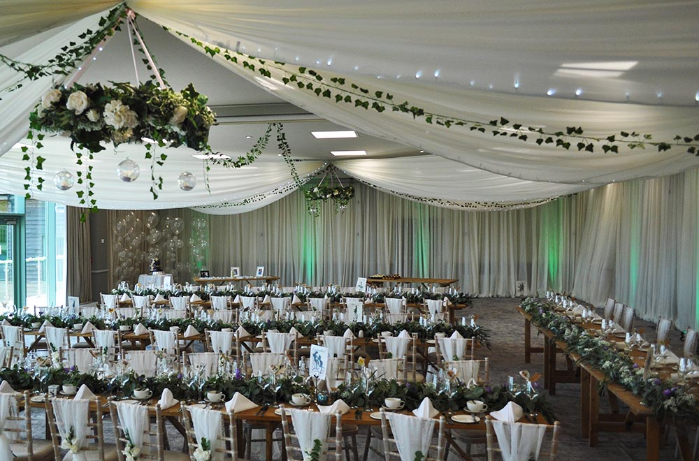 Ceiling drapery with floral foliage green leaf garlands and hanging floral hoops at De Vere Cotswold Water Park wedding