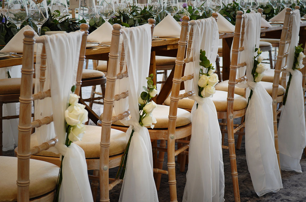 Wedding at DeVere Cotswold Water Park Hotel with wooden chairs and chiffon chair drops