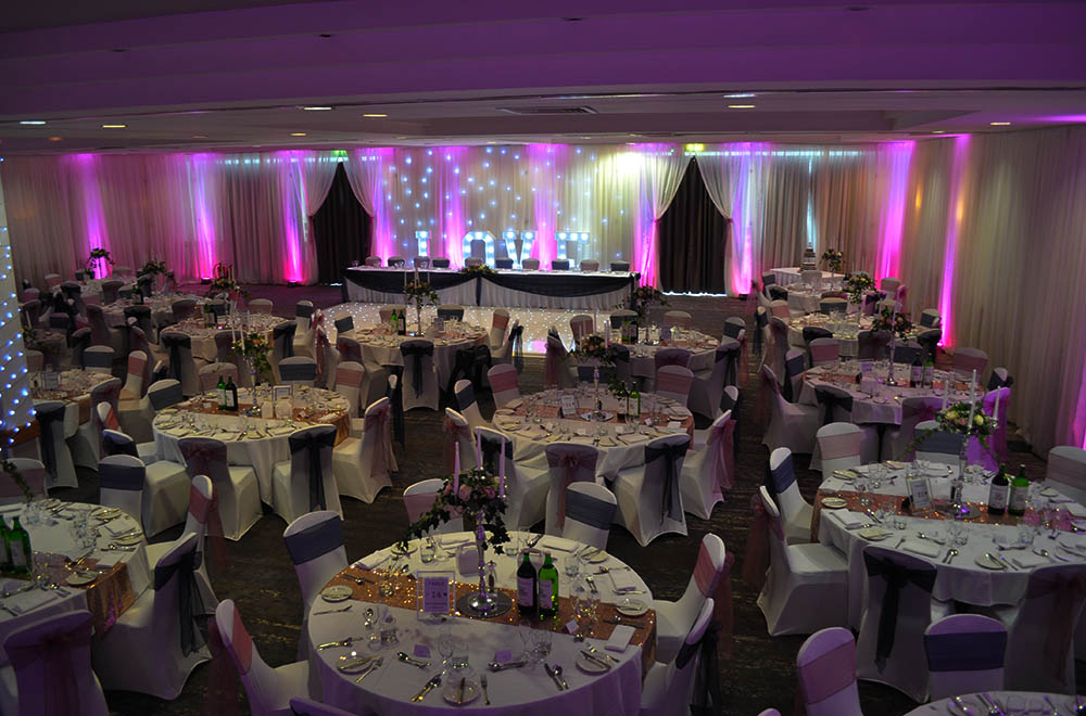 Pink and purple uplighters with room wall drapes for a wedding breakfast at the Double Tree Hilton Hotel in Swindon