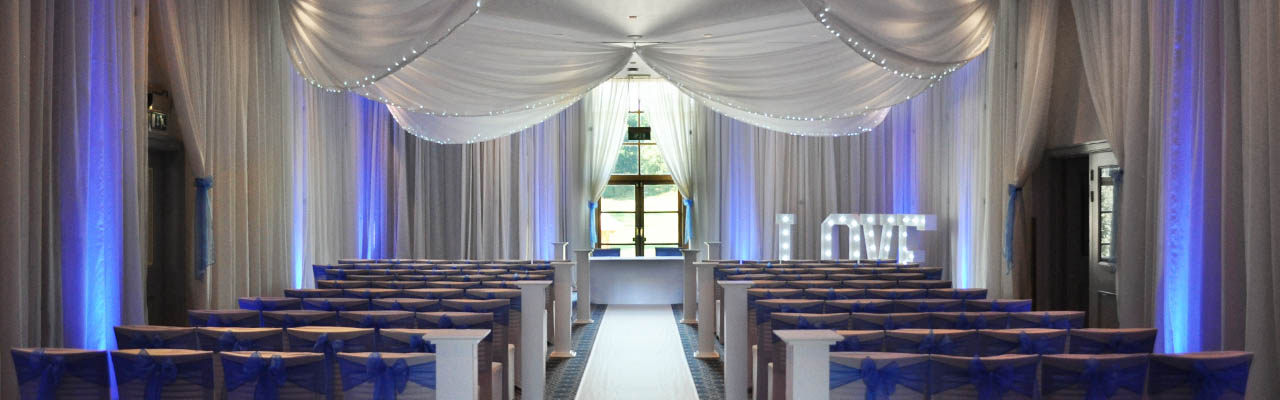 Wedding at Bowood Golf Club and Hotel with ceiling and wall drapes with blue uplighting