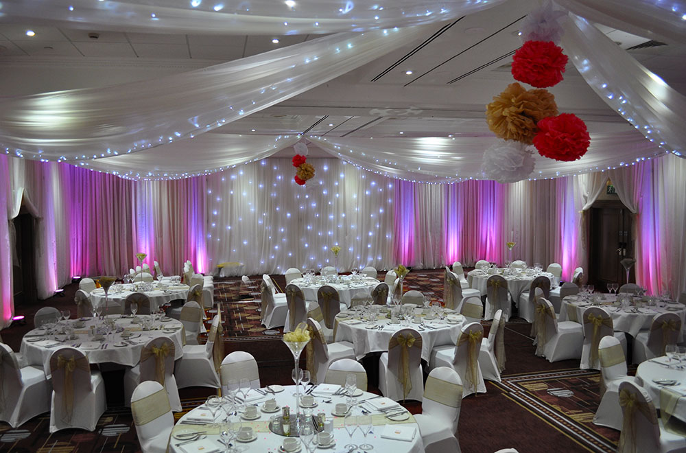 Wall and ceiling wedding drapery at the Marriott Hotel Swindon with pink uplighting on the drapes