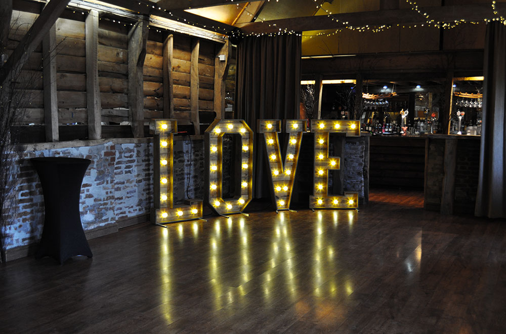 Large Wooden Rustic Love Letters at Wellington barn Wedding venue. With Warm White Fairground style LED bulbs.